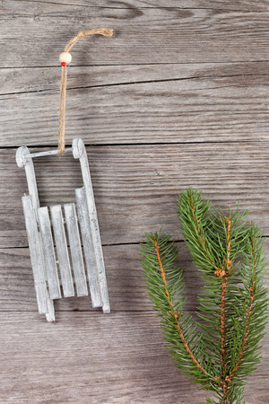fir twig: fir twig and sled hanging on wooden plank