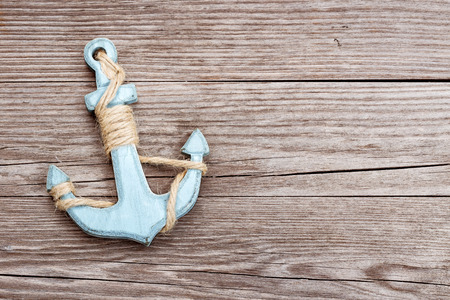 small blue anchor on a wooden background