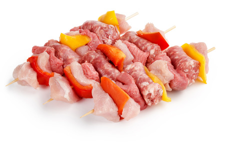 three raw meat skewers isolated on white background