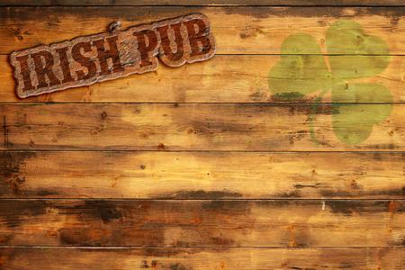 irish pub label and green shamrock on wooden background