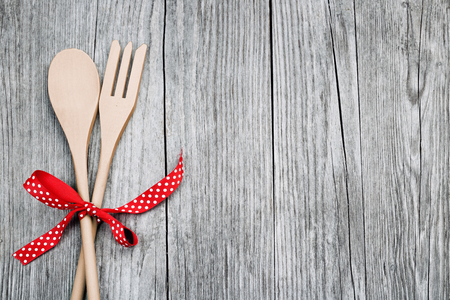red kitchen: wooden spoon and fork tied up with a red ribbon on rustic background Stock Photo