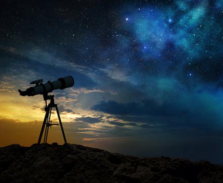 Melkweg bij zonsopgang en silhouet van een telescoop