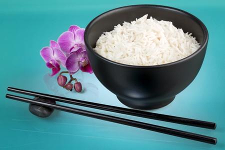 arroz blanco: tazón de arroz blanco, orquídeas y los palillos Foto de archivo