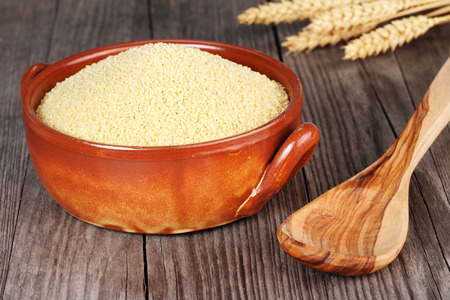 durum wheat semolina: couscous in an earthenware bowl and wooden spoon