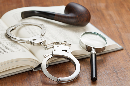handcuffs, magnifying glass and pipe over an open book Stok Fotoğraf - 50605784