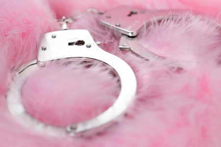 romance sex: handcuffs in a background of pink feathers