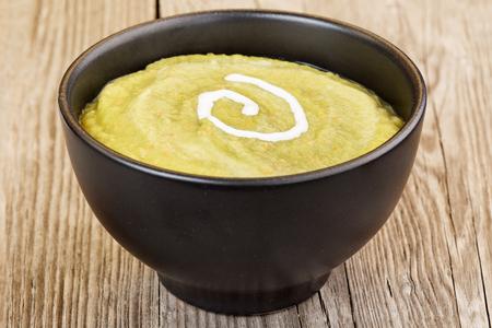 mash: vegetable mash in black bowl on wooden table Stock Photo