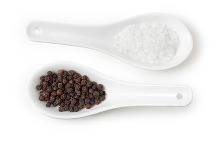 pepe nero: Due cucchiai di porcellana con sale e pepe isolato su bianco