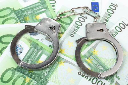 manacles: steel handcuffs on a heap of 100 euro banknotes