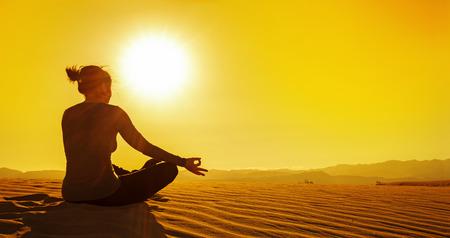 duna: mujer sentada en posición de loto en la duna de arena en la puesta del sol Foto de archivo