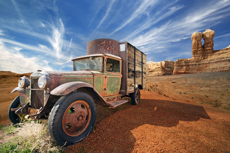 pick up: rusted abandoned truck in a rocky desert landscape