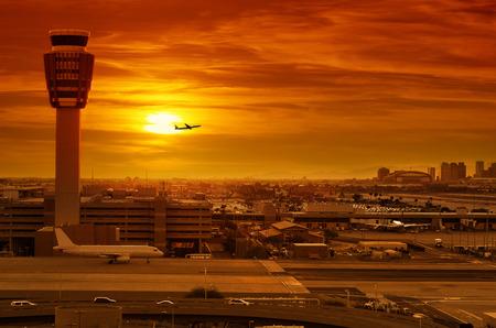 de luchthaven verkeerstoren en opstijgend vliegtuig bij zonsondergang