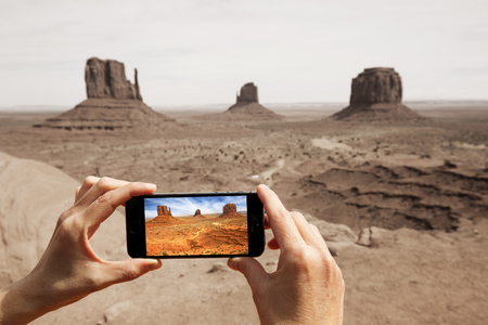 taking photograph: hands taking picture at the monument valley with a smartphone Stock Photo