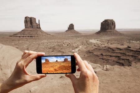manos tomar la foto en el valle del monumento con un smartphone
