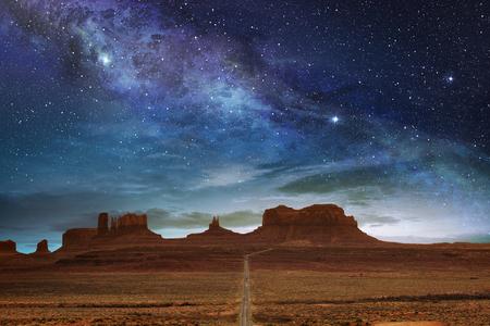 schilderachtige route naar het Monument Valley onder een nachtelijke sterrenhemel
