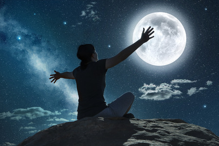 woman sitting and raising arms in the moonlight  Banque d'images