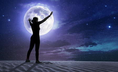female silhouette with outstretched arms in the moonlight Stock Photo