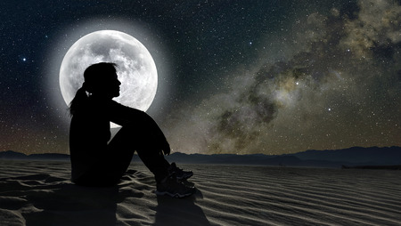 blue sky thinking: profile of a woman sitting on sand in the moonlight Stock Photo