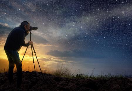 hombre tomando una foto al amanecer con cielo estrellado Foto de archivo