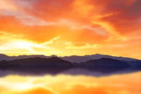scenic dawn on a mountain range reflecting in water