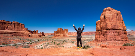 woman with raised arms facing monument valley