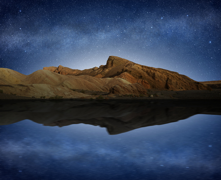 rocky hill reflected in water under a starry night sky Stock fotó