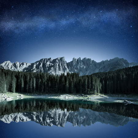 mountain range and fir forest reflecting in alpine lake at night