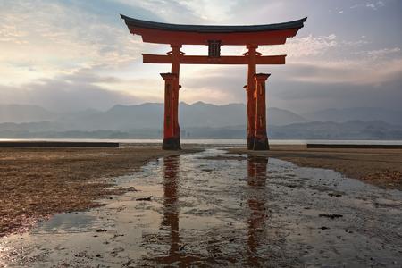 Torii of Itsukushima shrine with low tide at sunset Sajtókép