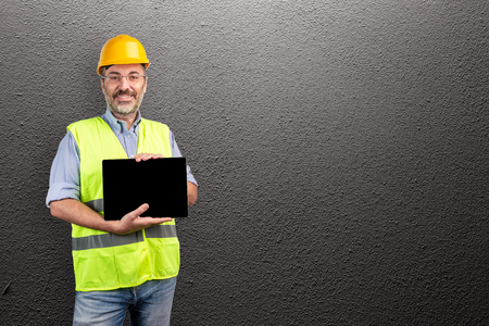 Construction industry professional showing a blank tablet isolated on a gray wall Stock fotó