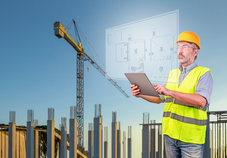 Architect holding a tablet displaying blueprint in a construction site