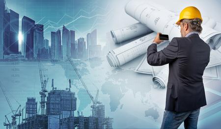 Architect holding a smartphone and blueprints Фото со стока