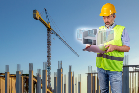 Architect in construction site with tablet displaying a hologram