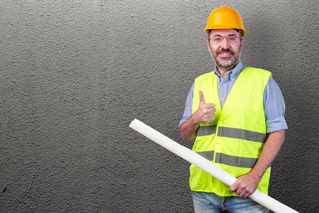 Construction worker holding blueprint against a grey wall