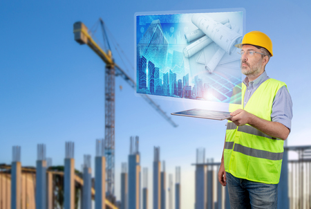 Engineer holding a tablet displaying construction plans in construction site