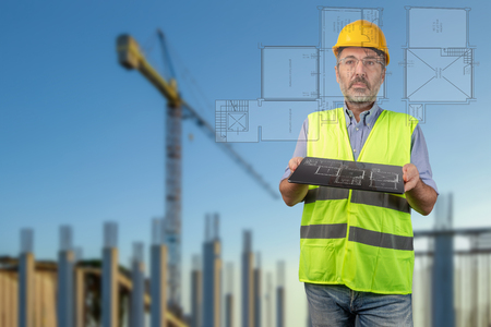 Surveyor holding a tablet displaying house layout in construction site