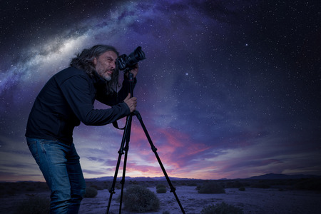 Man standing at camera on tripod under a starry sky