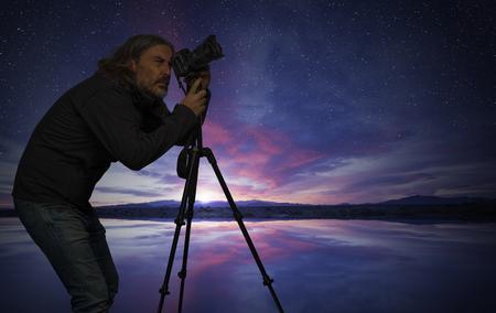 Man shooting photo along lake shore at dawn