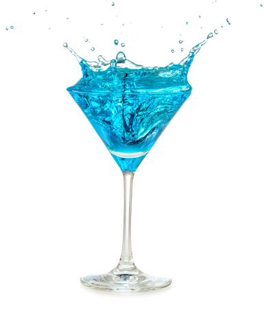 Blue cocktail splashing in martini glass isolated on white