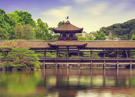 Wooden covered bridge reflected in pond water of  Heian jingu garden, Kyoto
