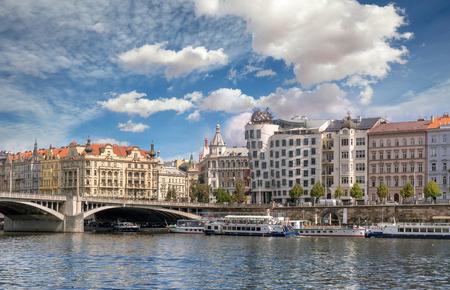 Dancing house, buildings and bridge on Vltava riverside in Prague, Czech Republic Фото со стока