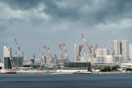 Crane and buildings in a construction site in Tokyo city bay area Фото со стока