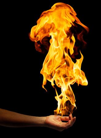 Female hand holding flames on black