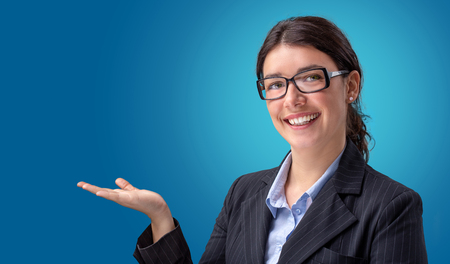 Smiling businesswoman showing empty hand isolated in blue