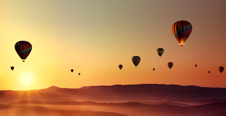 Hot-air-balloons at dawn over misty countryside