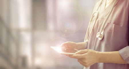 doctor using a digital tablet, half length portrait of a female physician in a blurred hospital background, concept of health care service professionals