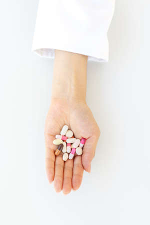 closeup of female doctor hand holding pills and capsules, pharmaceutical treatment concept