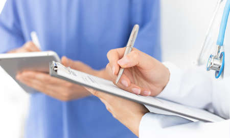 Health care professionals teamwork. Female doctor's hand holds a pen and writes on medical record, male doctor uses a digital tablet on blurred background