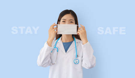 female asian doctor wearing a protective mask isolated on blue background with