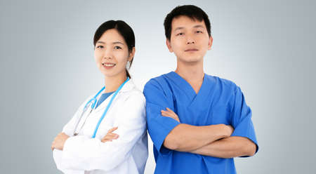 two smiling physicians in uniform, confident asian doctors looking at the camera, concept of clinic staff teamwork
