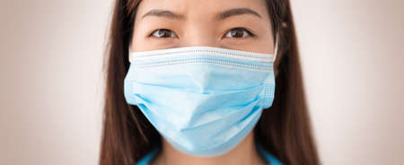 Closeup of asian woman wearing protective mask and looking at the camera. Concept of protect yourself and others from coronavirus contagion